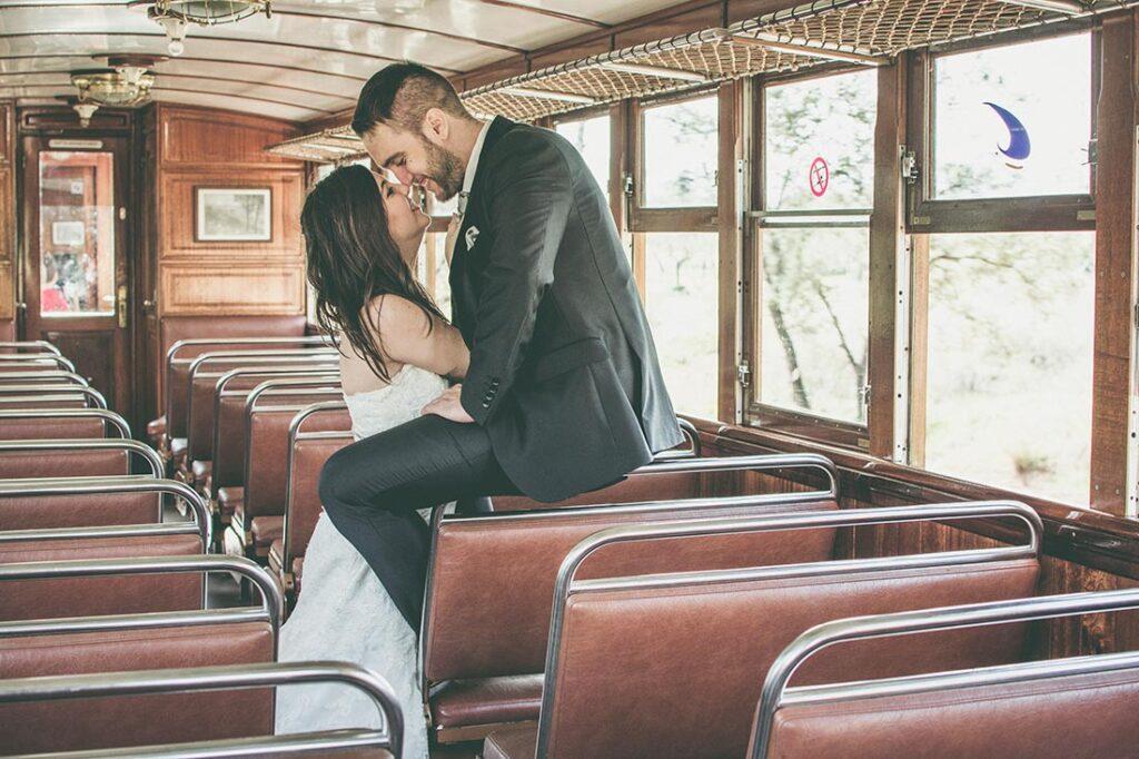 Una pareja se muestra en actitud romántica en el interior de uno de los vagones del tren de Sóller, de aspecto vintage.