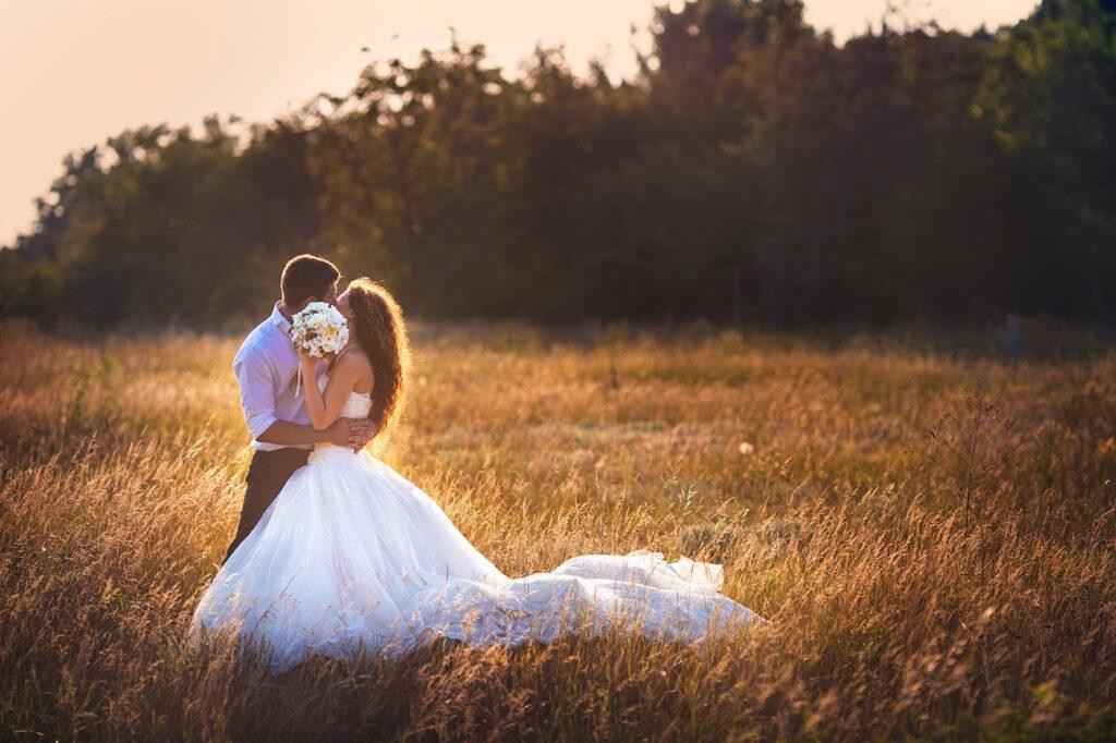 Escena campestre con una cálida atmósfera. Una pareja de novios se besa, mientras la novia oculta el rostro de ambos levantando el brazo con el ramo.
