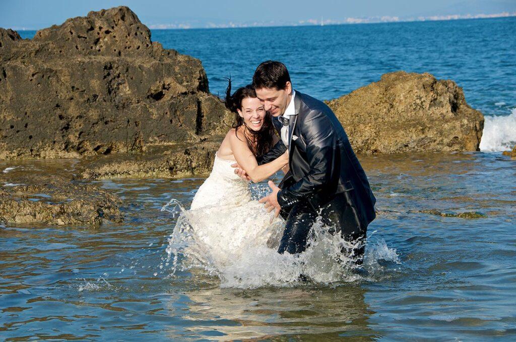 Fotografía de Boda divertida, donde una pareja de novios compiten dentro del agua. El juego consiste en llegar en primer lugar, para lo que se esfuerzan en correr mientras el agua les salpica hasta la cintura. Foto de Boda en la Playa del Coll d'en Rabassa.