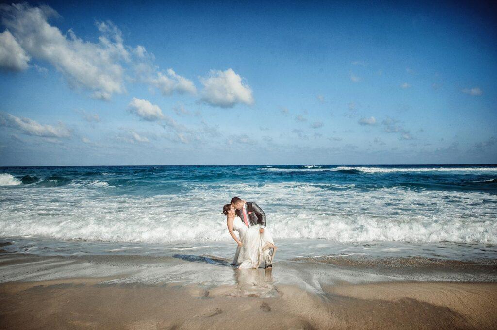 Foto de boda en la playa, donde la Novia se inclina hacia atrás mientras su novio la sostiene. A escasos dos metros, un volumen poco habitual de agua azul intenso y espuma les atrapará en cuestión de segundos.