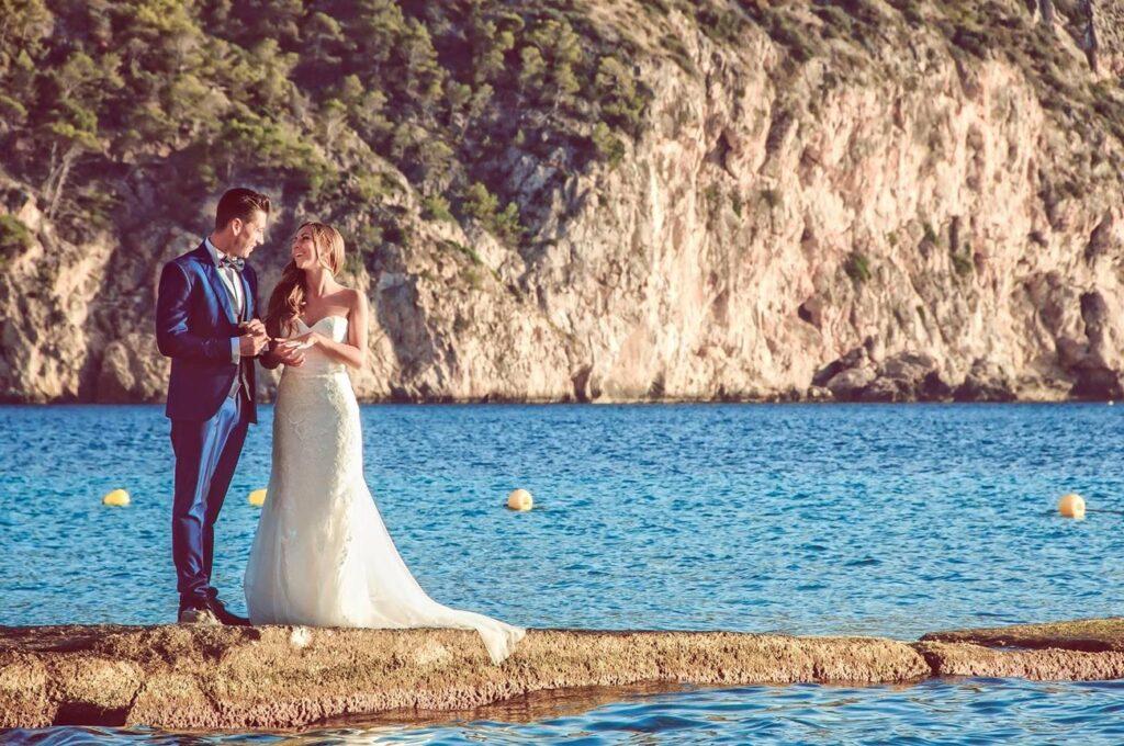 Simpática fotografía de post boda que representa a una pareja de novios sobre una roca que sobresale en el mar. De manera desenfadada y espontánea, rien y comentan algo sobre los anillos en sus manos. La atmósfera del atardecer colorea el agua y el acantilado del fondo con encanto.