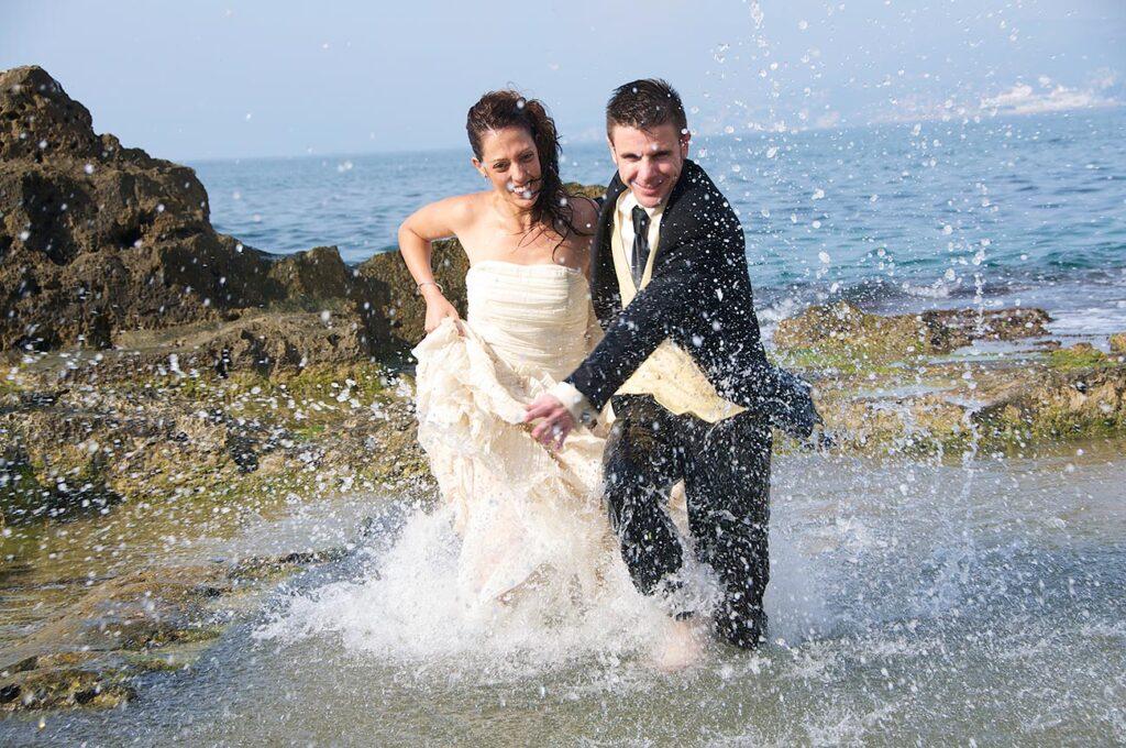Foto de reportaje post boda creativa y original de intensa acción. Una pareja de novios esprintan en la orilla de la playa. El agua salpica a su alrededor creando una textura que camufla y da intensidad a la escena.