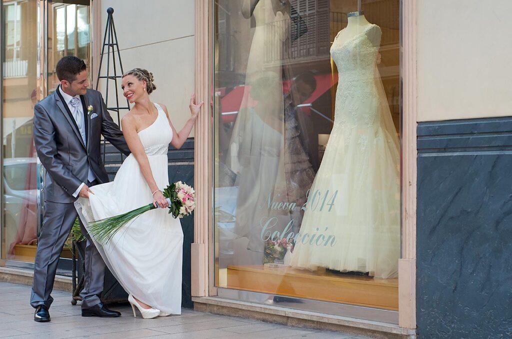 Una novia se para a observar el escaparate de la tienda de vestidos de novia donde adquirió el suyo.. El novio la intenta convencer para seguir su paseo. Típicas fotografías de boda originales de estilo urbano por excelencia.