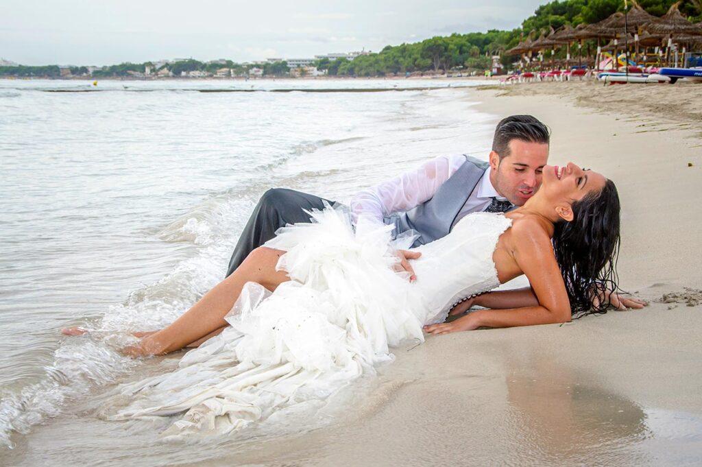 Foto de boda tomada en la playa de C'an Picafort. Los novios yacen en la arena, justo en la orilla donde no pueden estar a salvo del agua. La novia inclina la cabeza hacia atrás y expone su cuello al chico que hace gesto para besarlo.