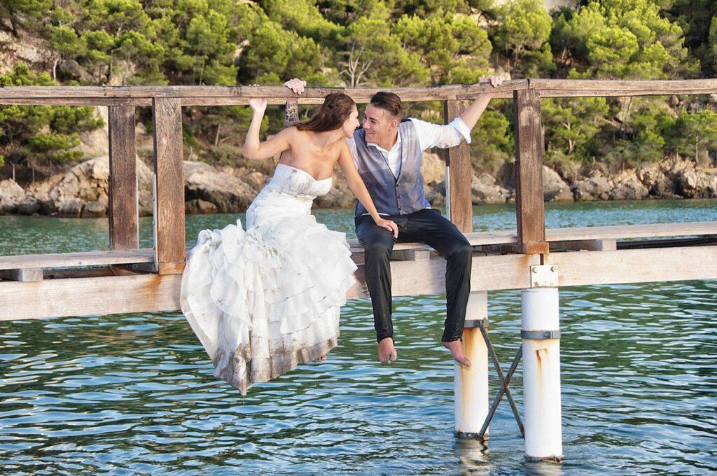Fotografía de Post Boda en la que aparece una pareja de novios sentados en un puente sobre el mar. Los pies cuelgan en el vacío, mientras se miran y se agarran a la barandilla de madera del puente. El agua tiene tonos verde azulados. Foto de Boda en la Playa de Camp de Mar.