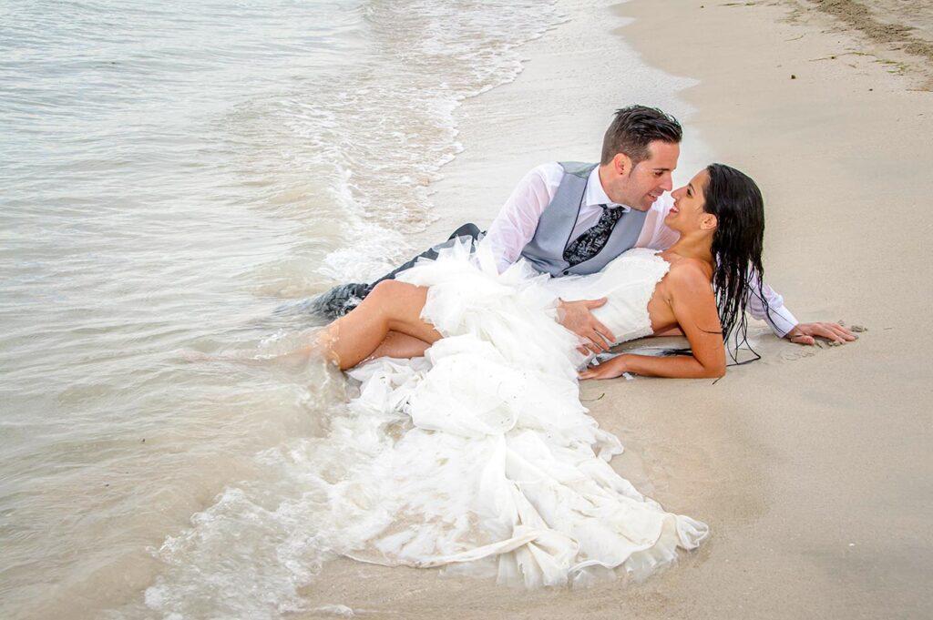 Novios yacen sobre la arena en la orilla de la playa. El agua moja sus pies y juguetea con los bajos del vestido de novia. El chico se coloca en una posición más elevada de manera que puede mirar cara a cara a la novia.