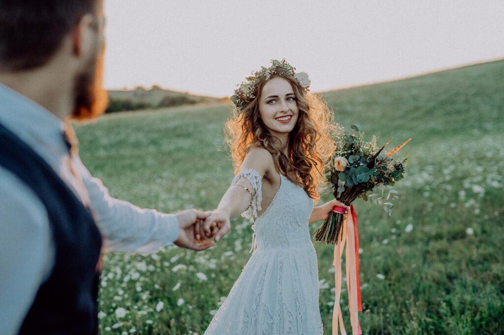 Imagen fascinante en una atmósfera de ensueño. Pareja de novios en el campo en un atardecer romántico. Ella extiende la mano mientras se gira hacia él.