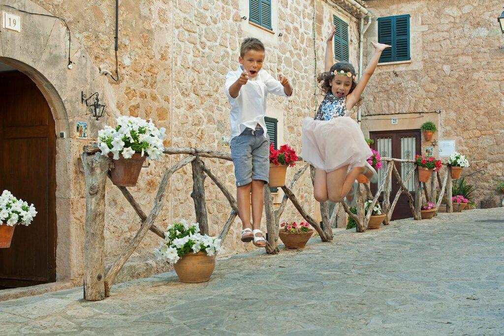 Dos simpáticos hermanos, niño y niña, saltan en una calle de Valldemossa, adornada con macetas de flores. La fotografía congela la acción en el momento en que se quedan suspendidos en el aire, el chico dirigiendo un gesto a la cámara y la pequeña levanta los brazos y dobla las piernas hacia atrás.