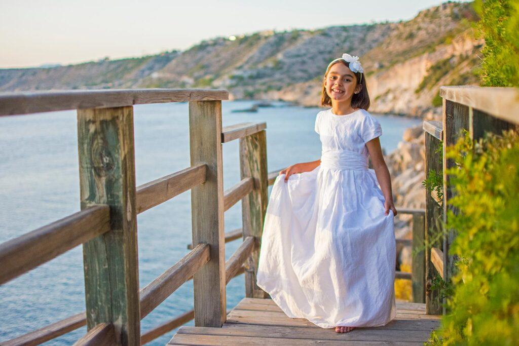 Acantilados de Cala Blava. En primer plano, antes de bajar la escalera de madera que conduce hasta la base del acantilado, una niña descalza y vestida de comunión presume de su vestido. Al fondo se distingue el océano de un azul claro.