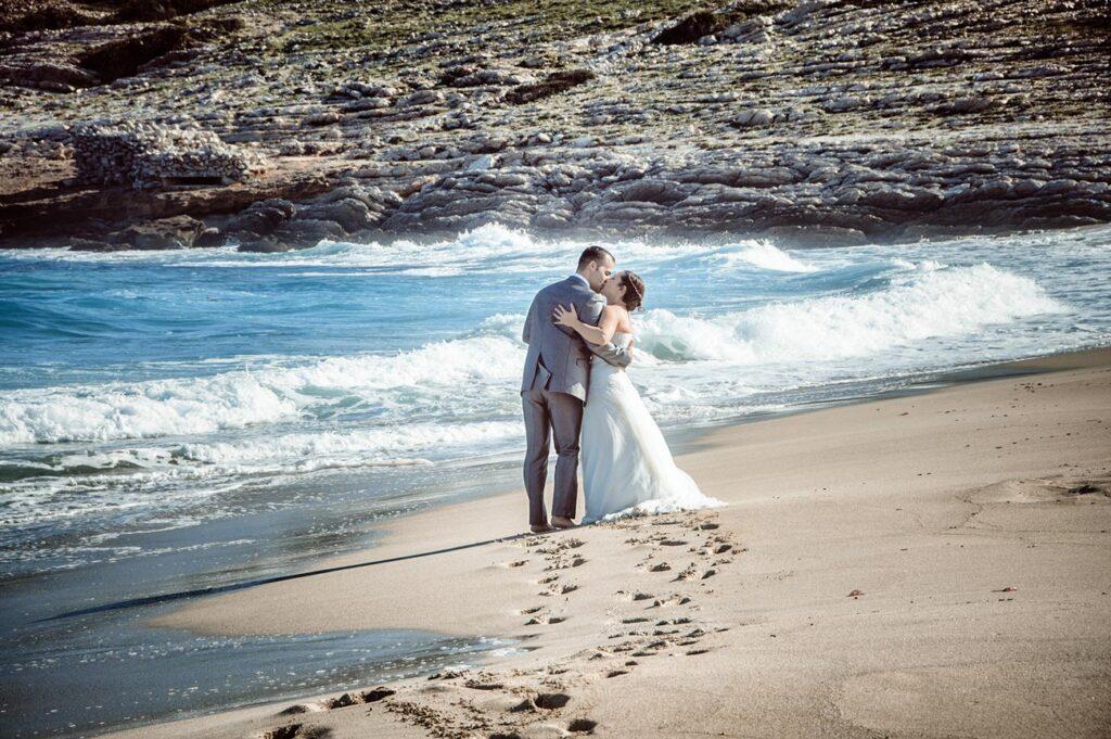 Una serie de huellas de pisadas en la arena conducen la visión de un observador hacia una pareja de recién casados que se besan al fondo. El mar de azul intenso baña con espuma la arena de la orilla. Una Fotografía de Boda muy original y creativa. Fotos de Boda en la Playa de Cala Mesquida