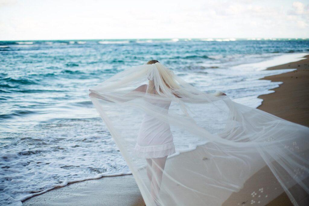 Chica extiende su velo del traje de boda, el cual se despliega por efecto de la brisa marina, mientras camina por la orilla de la playa.