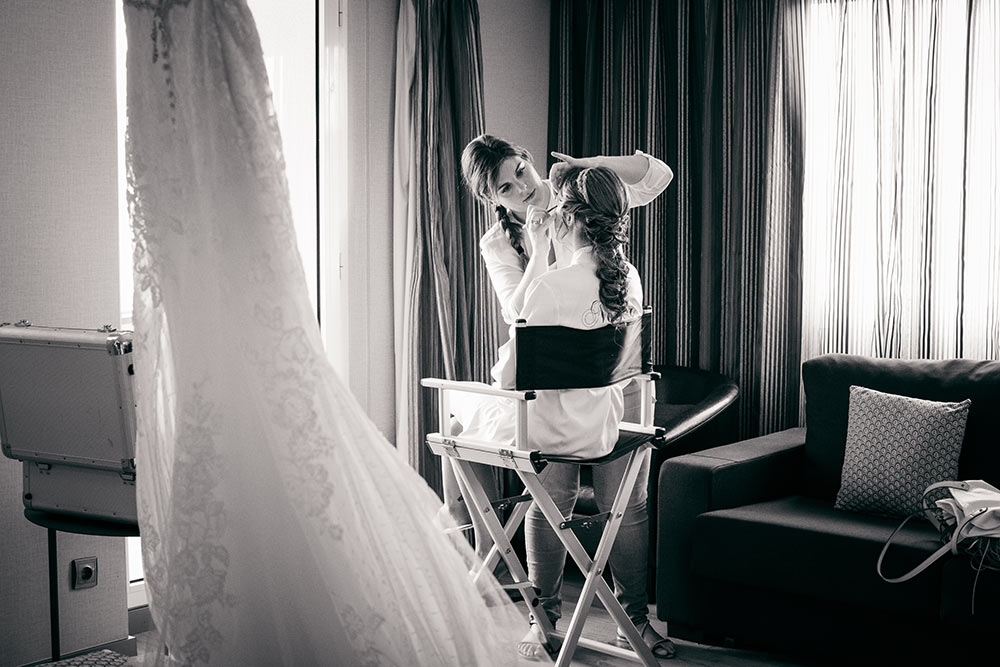 Estilista maquilla a la novia en habitación de hotel. El vestido de novia se dibuja en primer plano