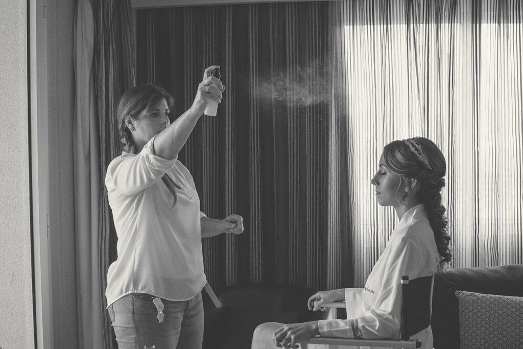 Estilista pulveriza fijador a la novia en habitación de hotel